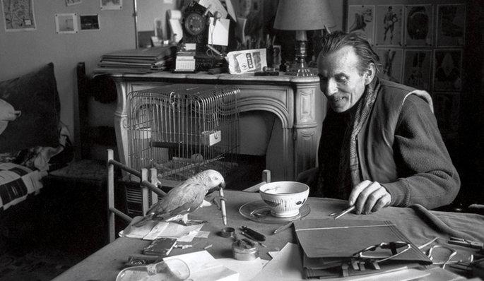 Portrait de l'écrivain Louis-Ferdinand Céline assis dans son domicile face à un bol de café.