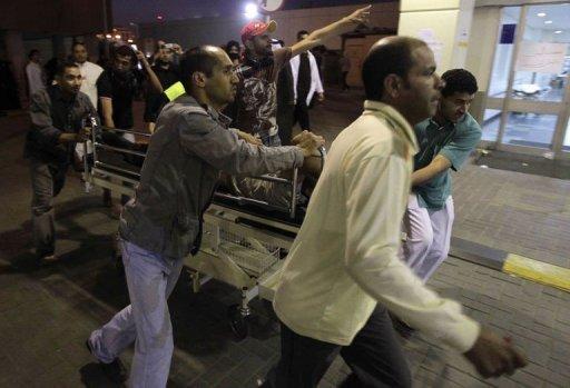 Evacuation d'un homme blessé le 18 février 2011 lors d'une manifestation à Manama