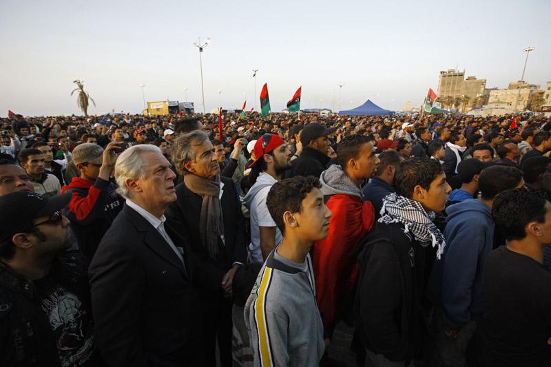 Sur la corniche de Benghazi, devant l'ex-Palais de justice, la population se rassemble tous les soirs à l'heure de la prière, pour manifester son soutien à la Révolution et écouter les nouvelles du front. Au centre, Gilles Hertzog et Bernard-Henri Lévy. © Marc Roussel