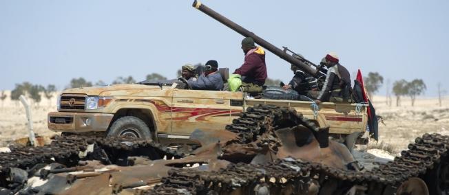 Des rebelles libyens devant un char des forces pro-Khadafi bombardé par l'Otan.C'est toujours la même histoire.