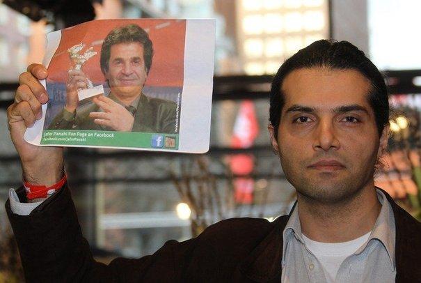 Un homme tient une photo du metteur en scène iranien Jafar Panahi lors du festival de cinéma de Berlin le 11 février 2011 afp.com/Valery Hache