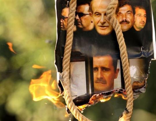 ©AFP / Patrick Baz Des portraits de l'ancien président syrien Hafez El Assad, de son fils Bashar El Assad et de leurs proches sont brûlés lors d'une manifestation