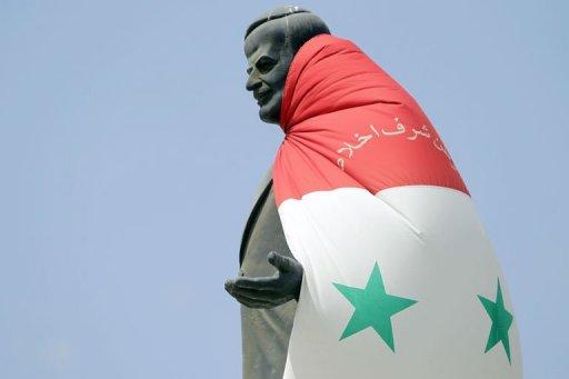 Drapeau syrien sur la statue de Hafez al-Assad, à l'entrée d'Homs (Syrie), le 30 août 2011 © AFP/Archives, Joseph Eid