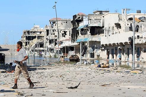Un rebelle avance dans le centre de Syrte, en ruine, samedi dernier.