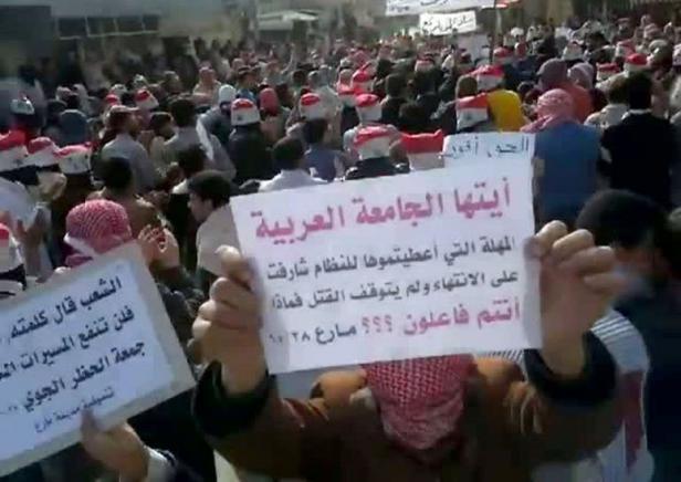 Capture d'écran d'une vidéo diffusée le 28 octobre 2011 sur YouTube de manifestants anti-régime à Alep avec des pancartes s'adressant à la Ligue arabe.