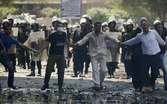 Des manifestants tentent de mettre fin aux affrontements entre police et mécontents près de l'ambassade américaine, au Caire, le 14 septembre 2012.