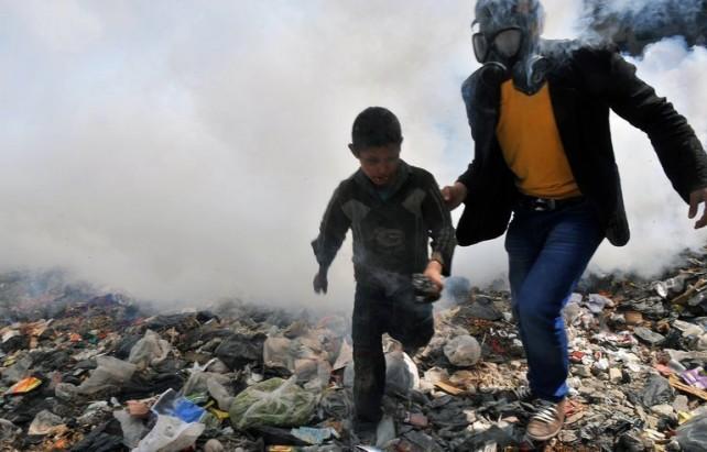 Un homme équipé d'un masque à gaz et un jeune garçon courent dans une rue d'Alep, dans le nord de la Syrie, en mars 2013.