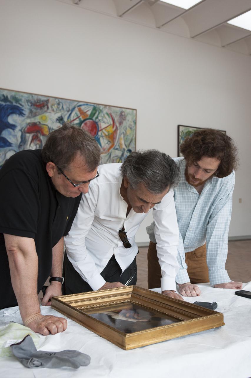 """Olivier Kaeppelin, Bernard-Henri Levy et Tancrède Hertzog devant """"L'invention de l'art du dessin"""" de Joseph-Benoît Suvée."""