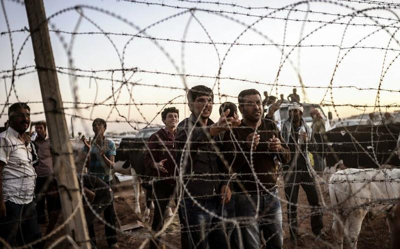 Des réfugiés kurdes de Syrie demandent de l'eau à des soldats turcs