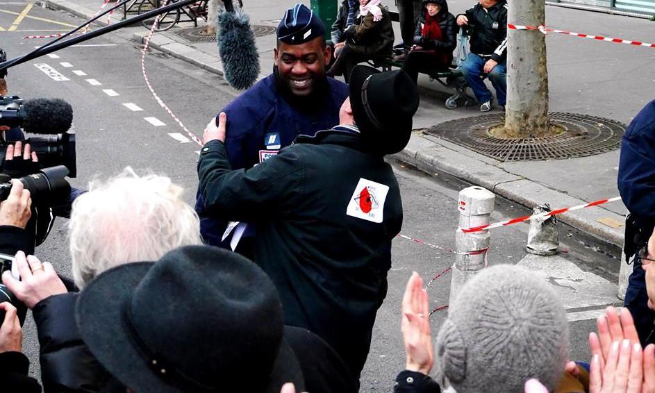 Accolade entre un manifestant et un policier lors de la manifestation de dimanche à Paris.