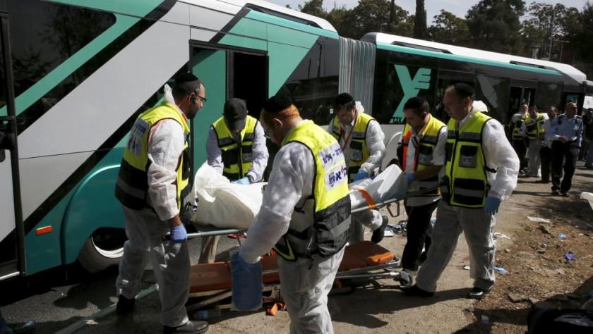 Les équipes de secours sortent le corps sans vie d'un passager du bus attaqué à l'arme à feu par deux individus, le 13 octobre 2015. REUTERS/Ronen Zvulun