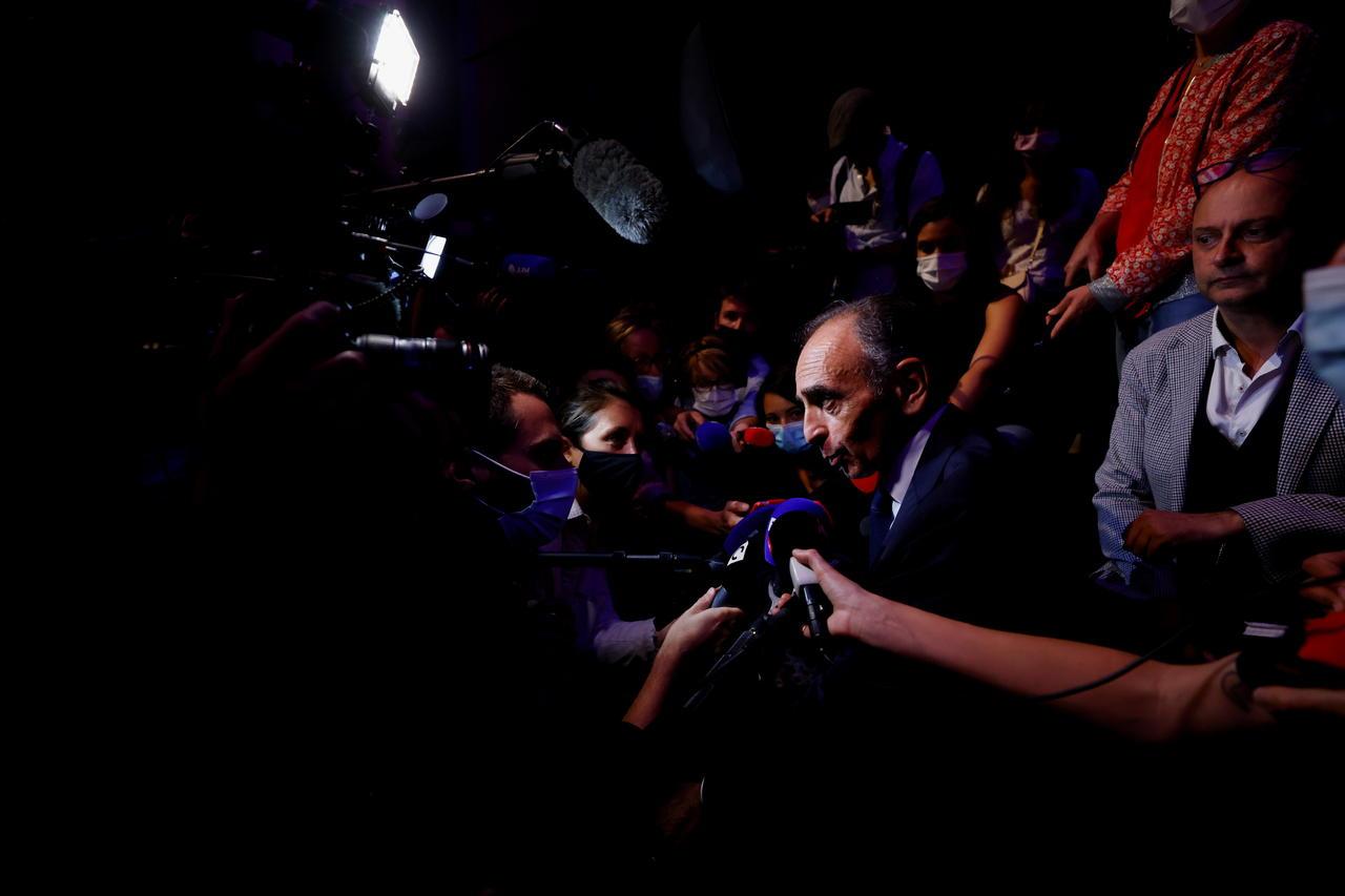 Portait d'Éric Zemmour s'exprime entouré par des journalistes.