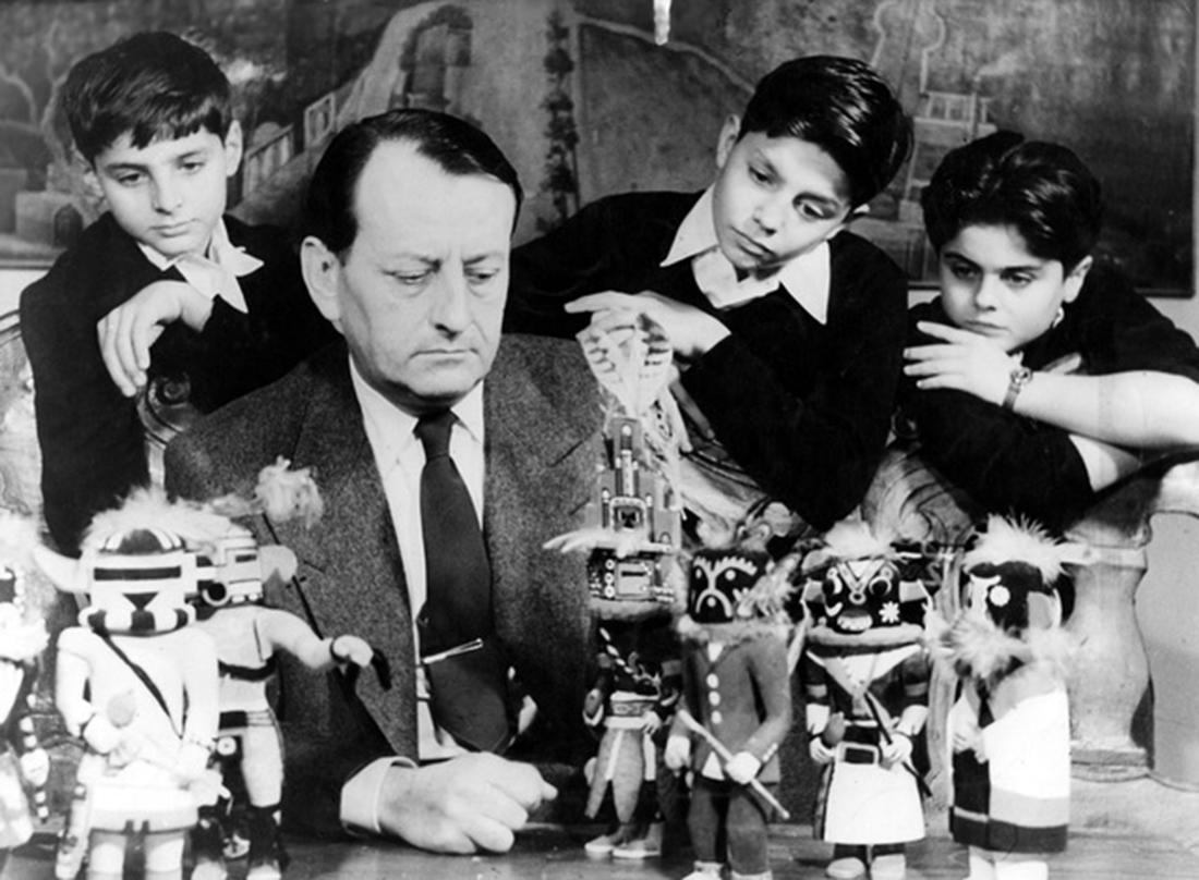 """André Malraux posant devant des poupées """"Kachina"""" (des Indiens Hopis au Nouveau-Mexique) ramenées pour ses fils Vincent et Gauthier et son neveu Alain qui l'entourent."""