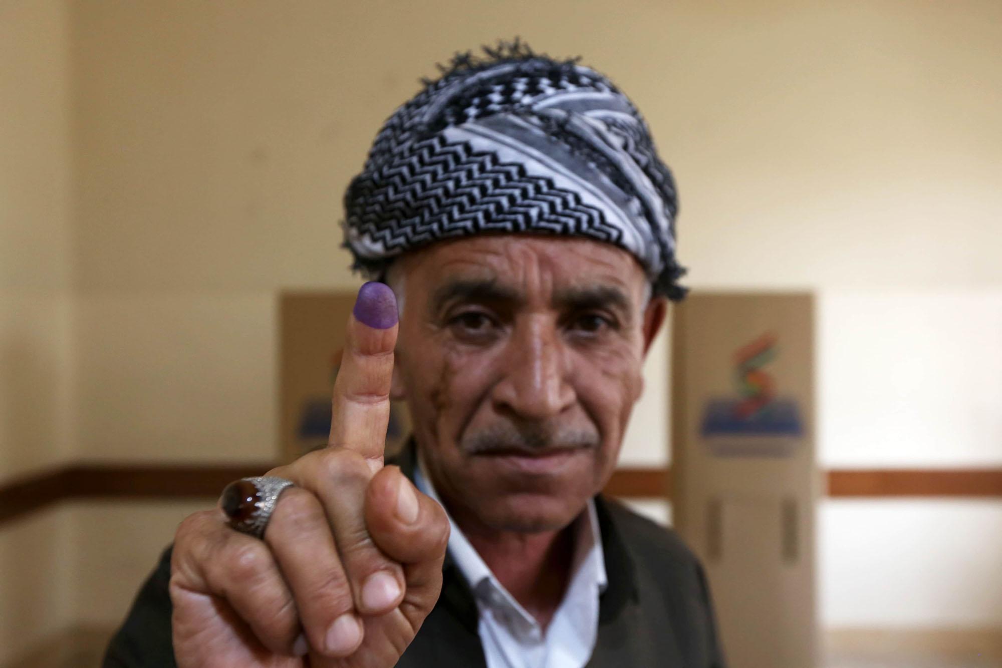 Un homme montre son doigt taché par l'encre, après avoir voté lors du référendum Kurde, le 25 septembre 2017.