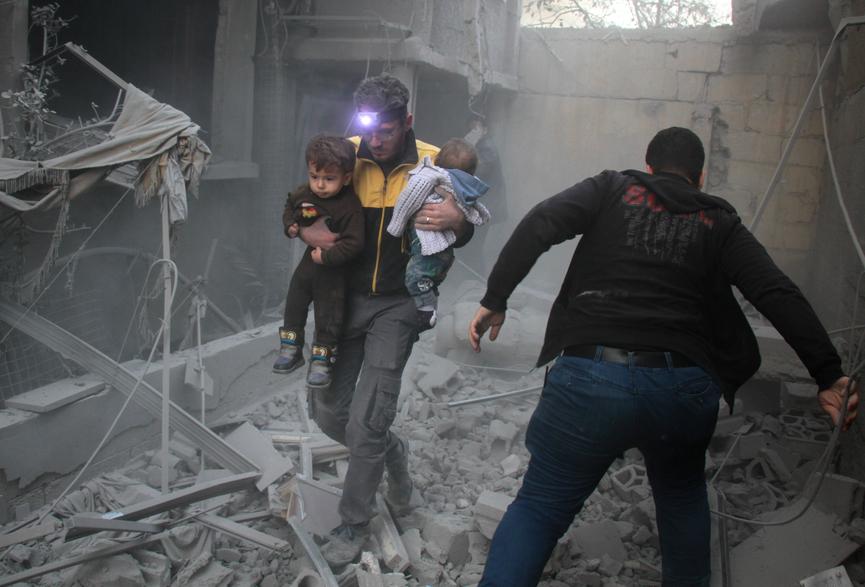 Un homme porte deux enfants après des bombardements à Douma, dans la région de la Ghouta en Syrie. Crédit : Hamza Al-Ajweh / AFP