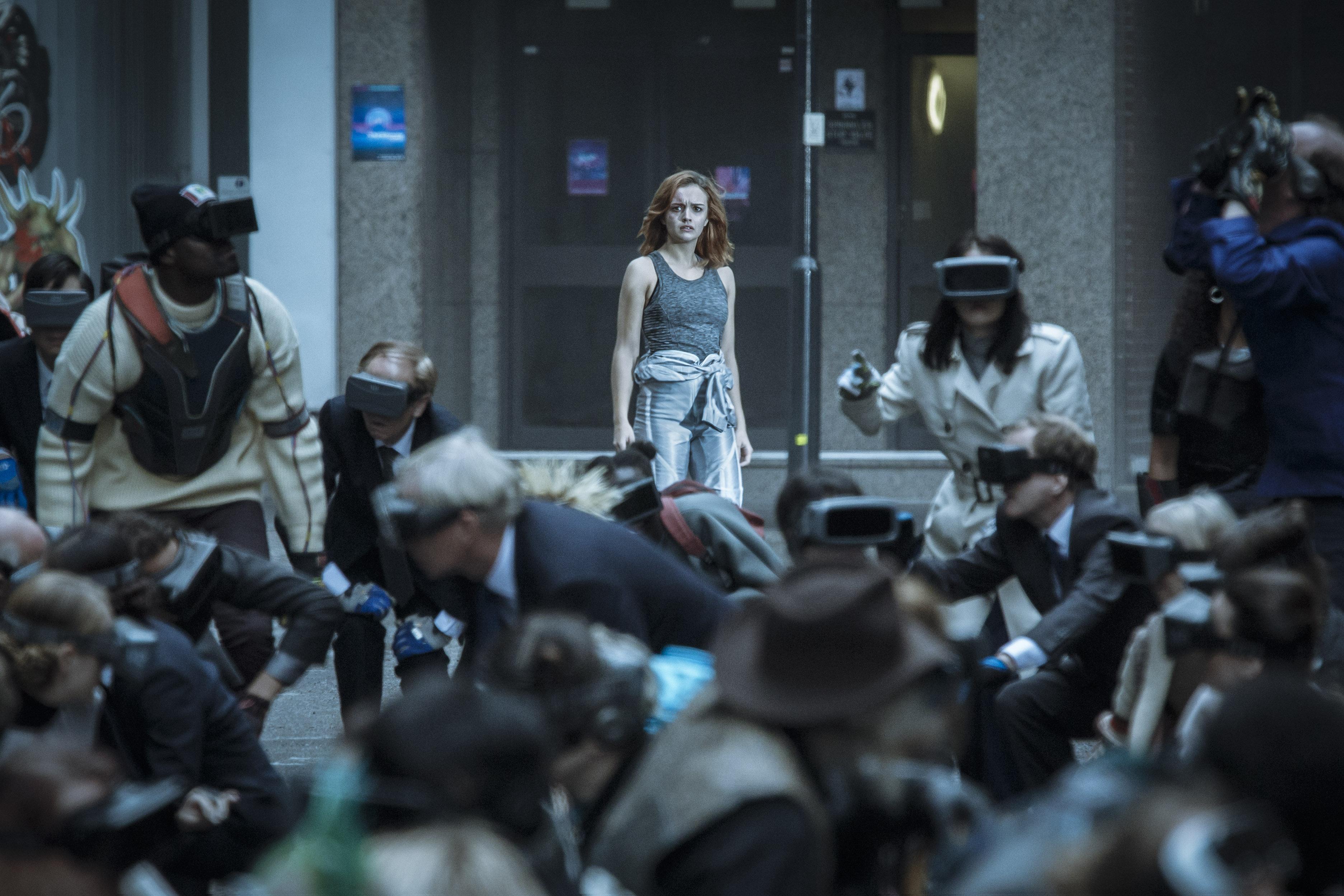 Samantha Cook (interprétée par Olivia Cooke) au milieu de joueurs concentrés sur la course qui a lieu dans l'Oasis virtuelle. Scène du film Ready Player One de Steven Spielberg.