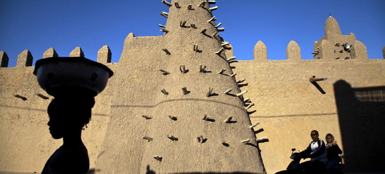 Des résidents de Tombouctou passent devant l'une des structures architecturales historiques qui ont permis à Tombouctou d'obtenir la désignation de site du Patrimoine mondial par l'UNESCO : la mosquée Djingareyber. Photo ONU/Marco Dormino