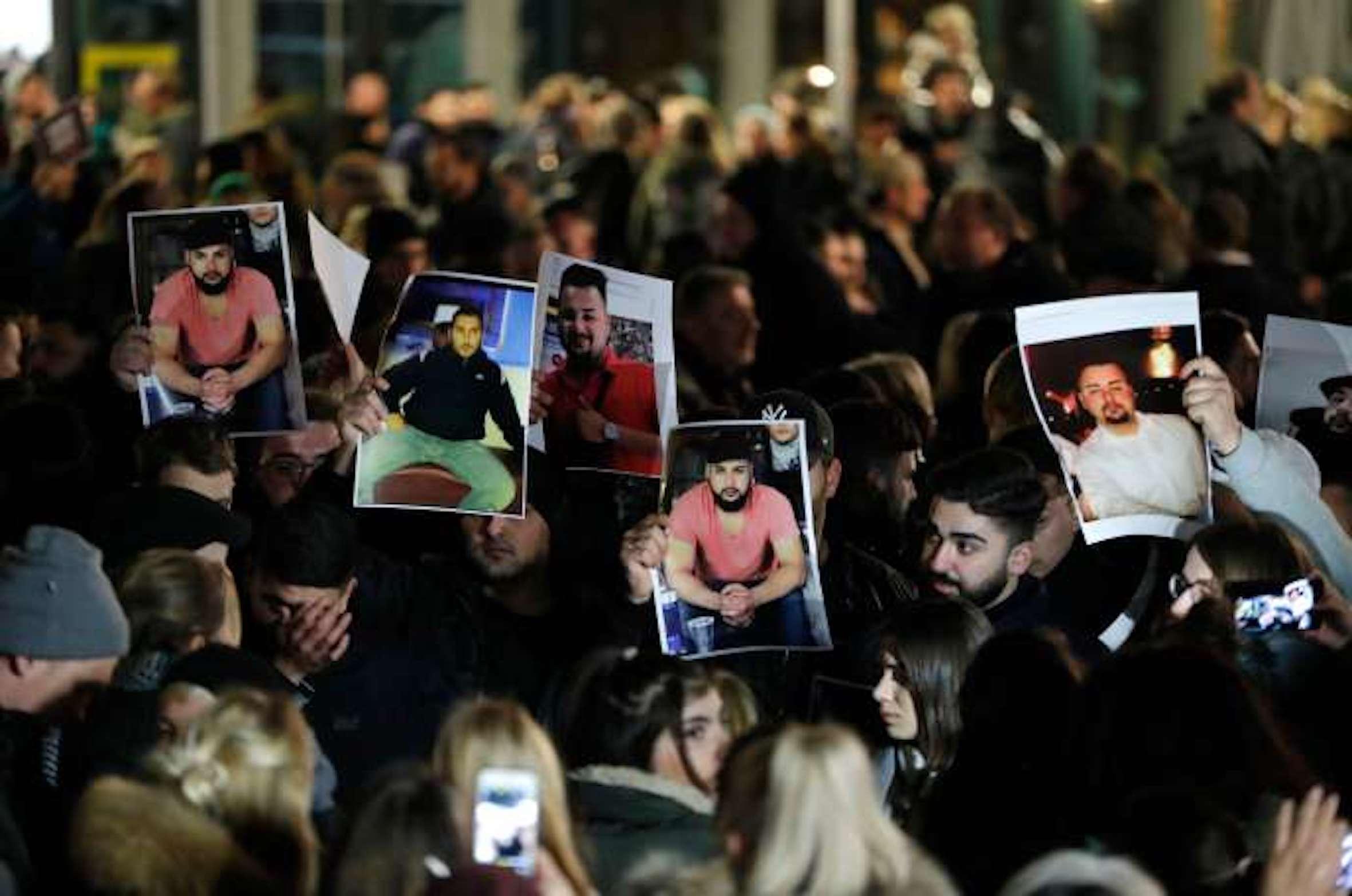 Des personnes en deuil brandissent des photos de victimes, lors d'une veillée près de Hanau (Allemagne), le lendemain des fusillades où neuf personnes ont été tuées, le 20 février 2020.