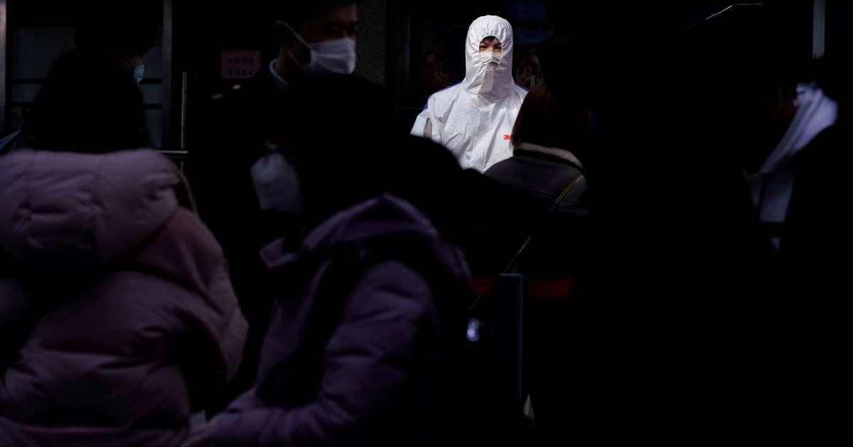 Une personne en uniforme de protection anti-Coronavirus à une gare de train de Shanghai.