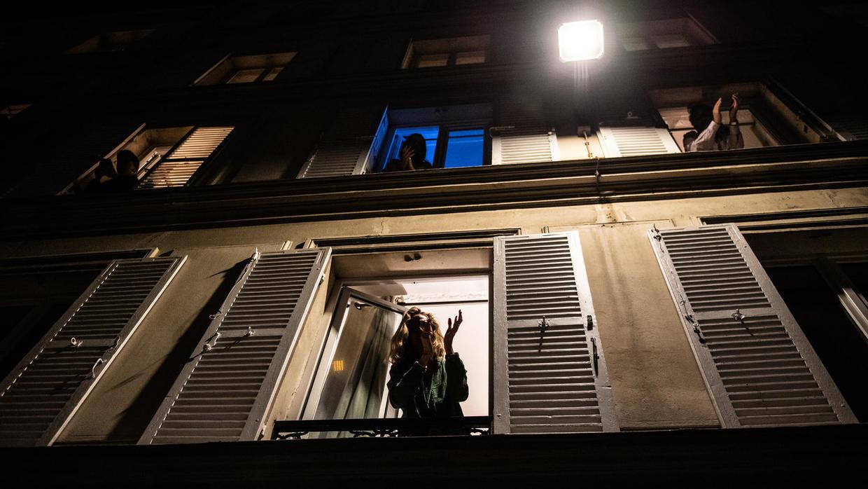 Des résidents confinés dans un immeuble parisien applaudissent depuis leur fenêtre le personnel soignant qui se bat contre l'épidémie déclenchée par le Coronavirus.