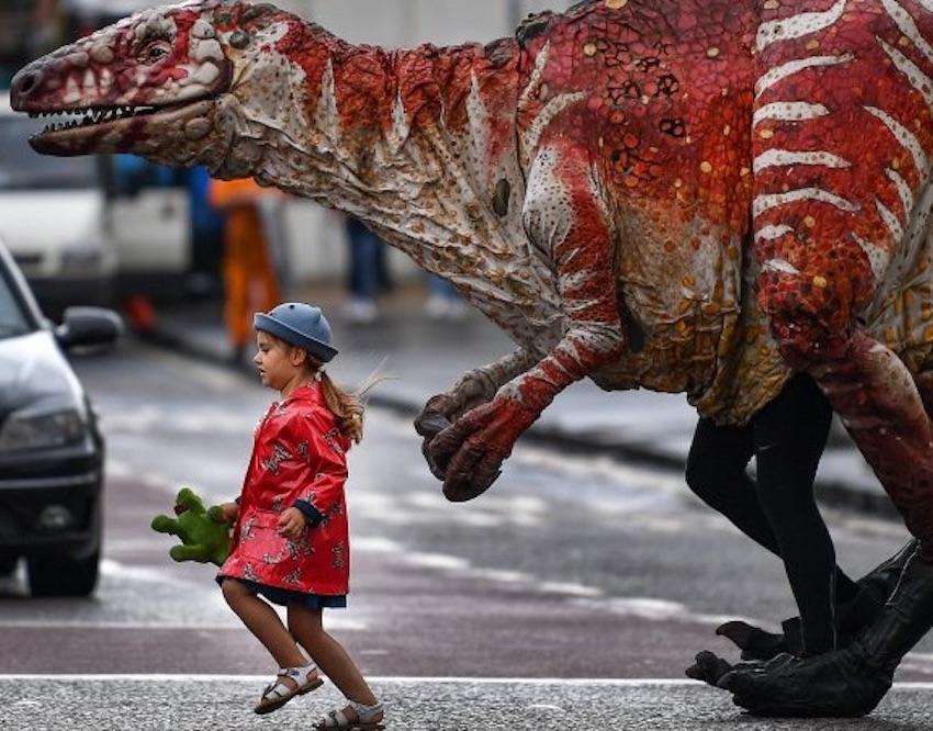 Une petite fille traverse la rue avec une marionnette incarnant un dinosaure.
