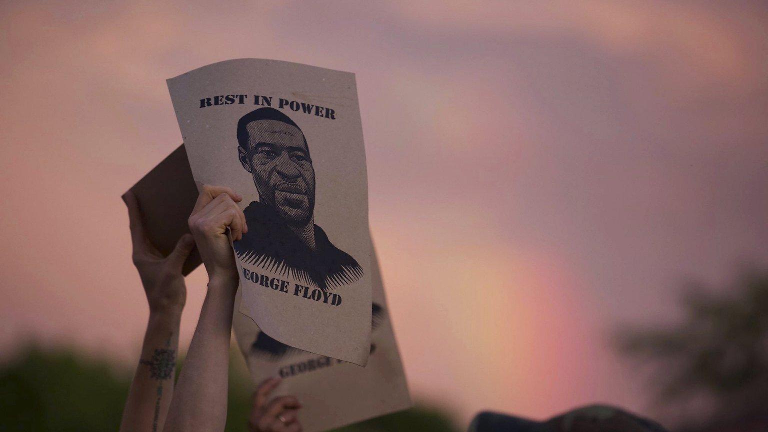 Des mains brandissent des images en hommage à George Floyd.