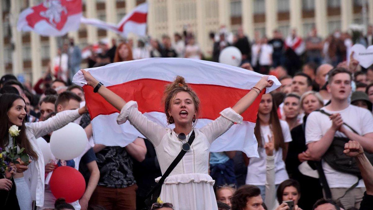 Une manifestante brandit l'ancien drapeau de la Biélorussie indépendante lors d'une manifestation contre le président Alexandre Loukachenko à Minsk, le 14 août 2020.