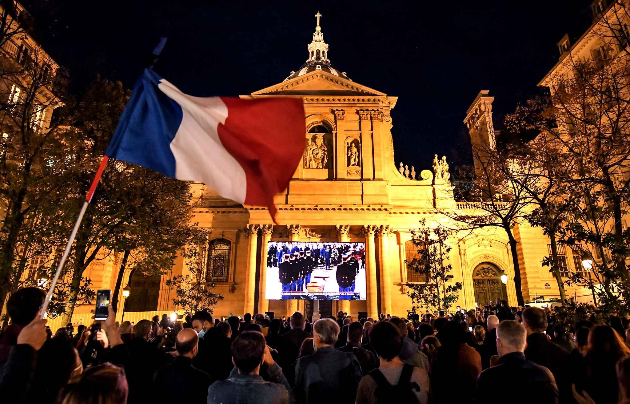 Vue de l'extérieur de la Sorbonne (Paris), au pied d'un écran géant retransmettant la Cérémonie d'hommage à Samuel Paty.