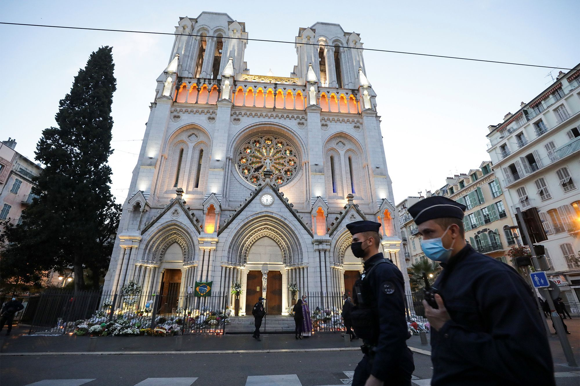 Des policiers marchent devant l'église Notre-Dame avant une messe pour rendre hommage aux victimes d'une attaque meurtrière au couteau à Nice, France, le 1er novembre 2020.