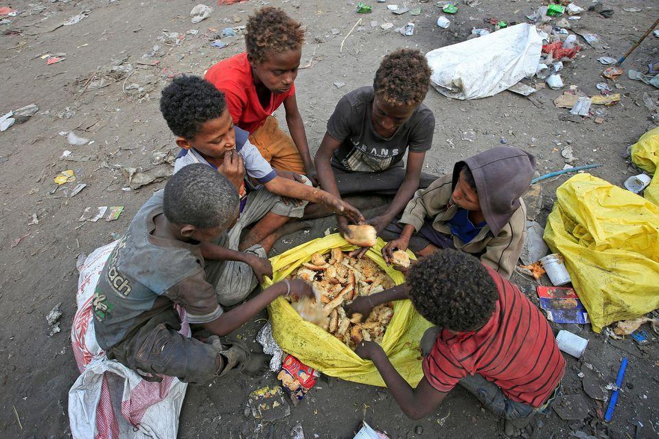 Des garçons mangent du pain ramassé dans les ordures, à Hodeida, en janvier 2018.