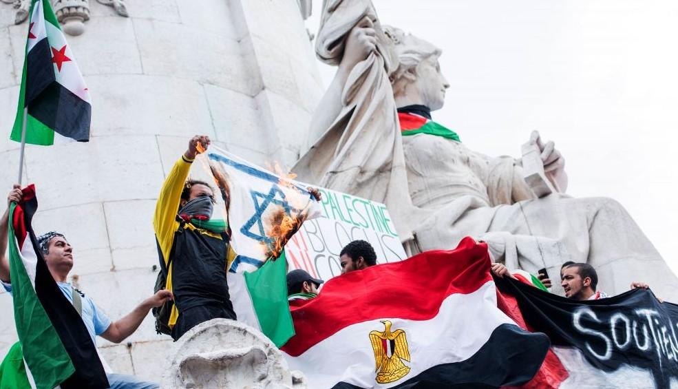 Un manifestant pro-palestinien brandit un drapeau israélien en feu lors d'une manifestation sur la place de la République à Paris, en France, le 26 juillet 2014.