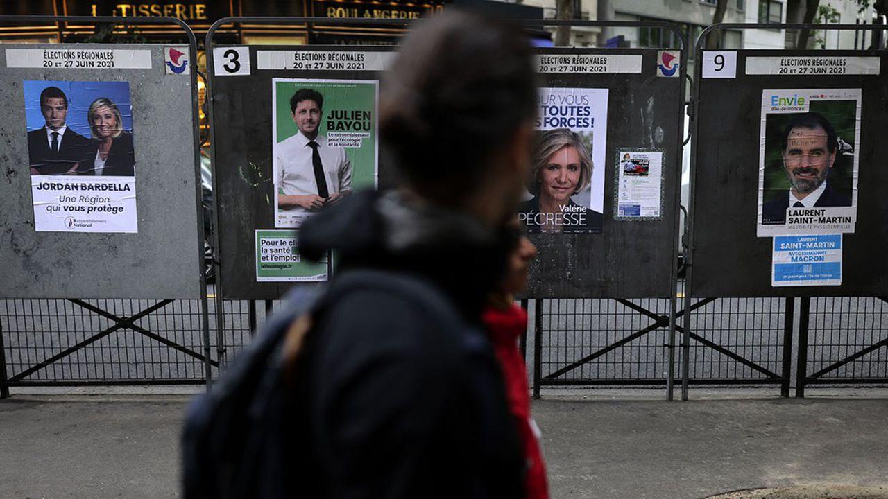 Un homme passe devant des affiches de campagne électorale, à Paris, le 24 juin 2021.