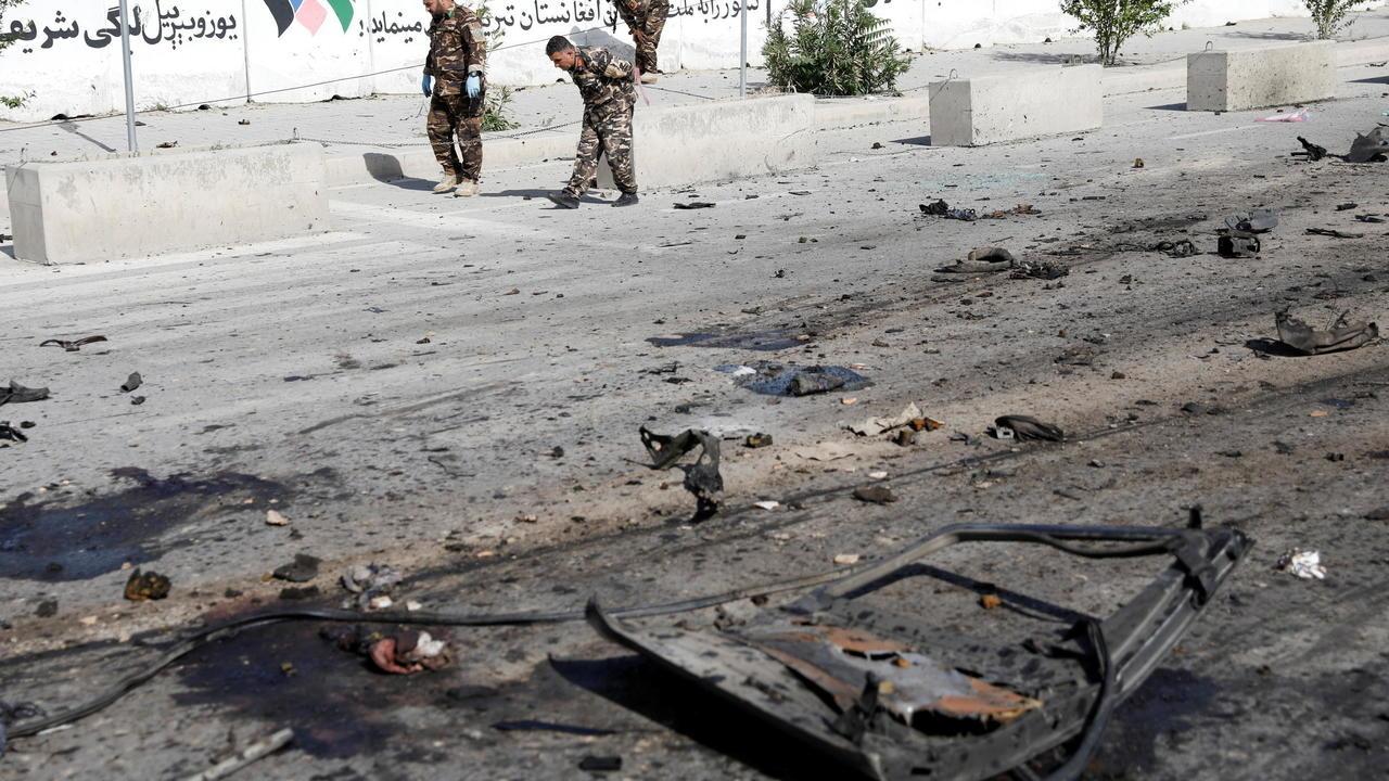 Les forces de sécurité inspectant les lieux de l'explosion d'un minivan à Kaboul le 3 juin 2021. Plusieurs attentats ont visé des véhicules de ce type ces dernières semaines, suite à l'annonce du retrait américain.