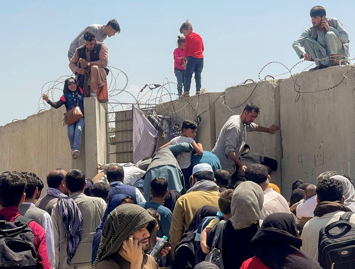 Un homme tire une fille pour entrer dans l'aéroport international Hamid Karzai de Kaboul, en Afghanistan, le 16 août 2021.