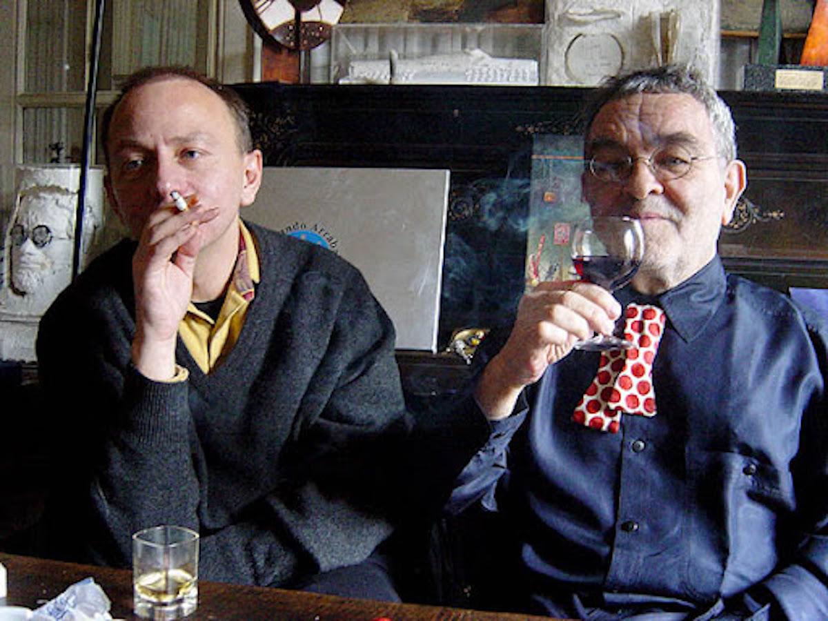 L'écrivain Michel Houellebecq fume tandis que Fernando Arrabal boit un verre de vin au domicile de ce dernier.