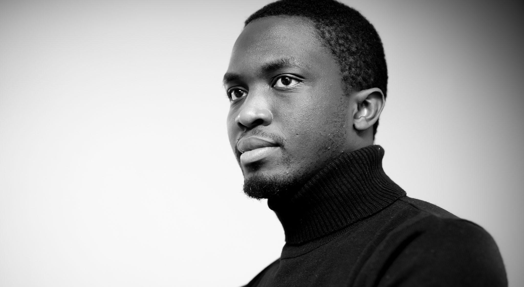 Portrait en noir et blanc de Mbougar Sarr Mohamed, l'écrivain sénégalais.