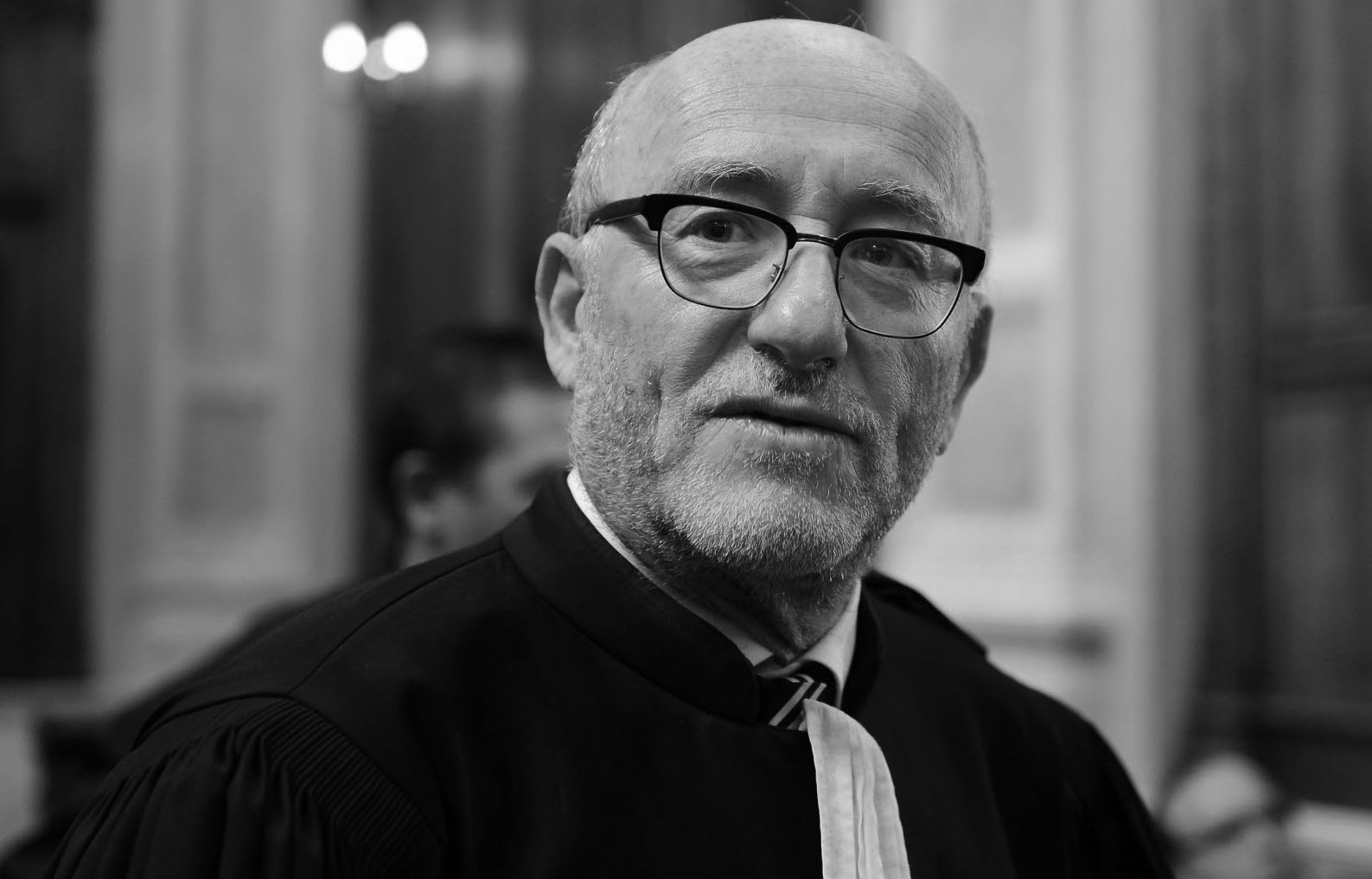 Portrait en noir et blanc de l'avocat Alain Jakubowicz, alors que ce dernier sort d'un procès au sein de la 17e chambre du Tribunal de Paris.
