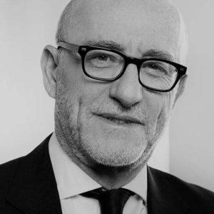 Portrait en noir et blanc de l'avocat Alain Jakubowicz, portant un costume et lunettes.
