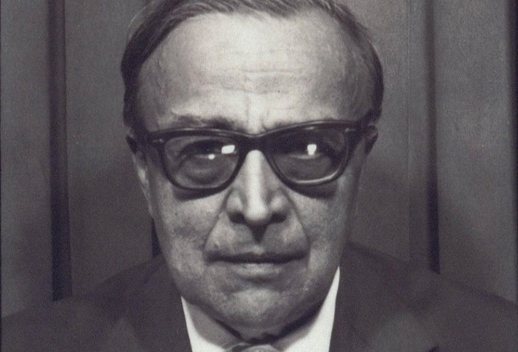 Portrait en noir et blanc du philosophe russe Alexander Kojève portant des lunettes.